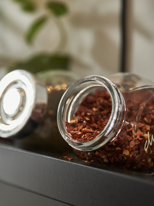 A close-up of an open IKEA RAJTAN glass spice jar with a red/orange coloured dried spice spilling out.