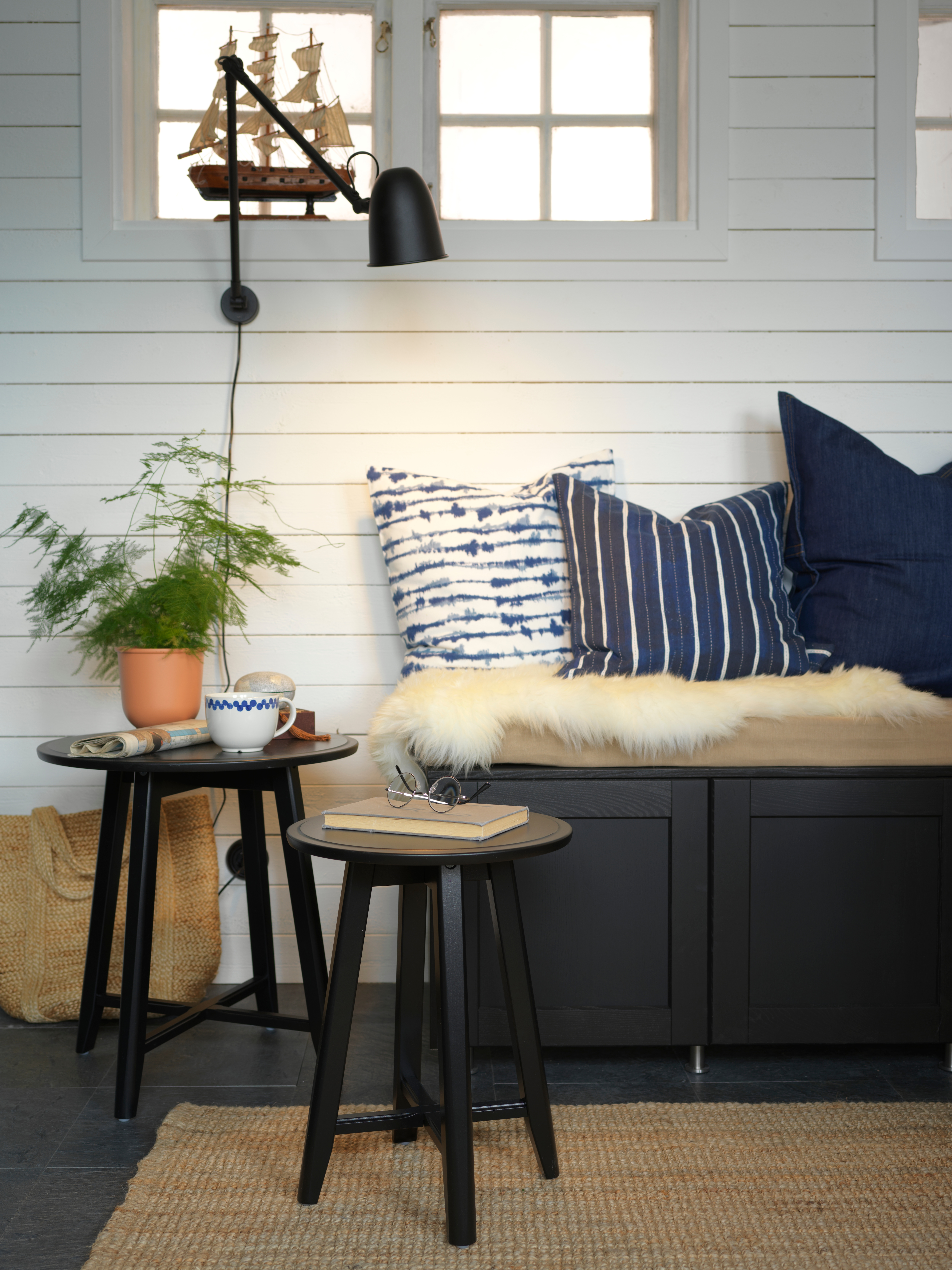 A wall with a lamp, bench and cushions by black KRAGSTA nest of tables holding a mug, potted plant, a book and eyeglasses.