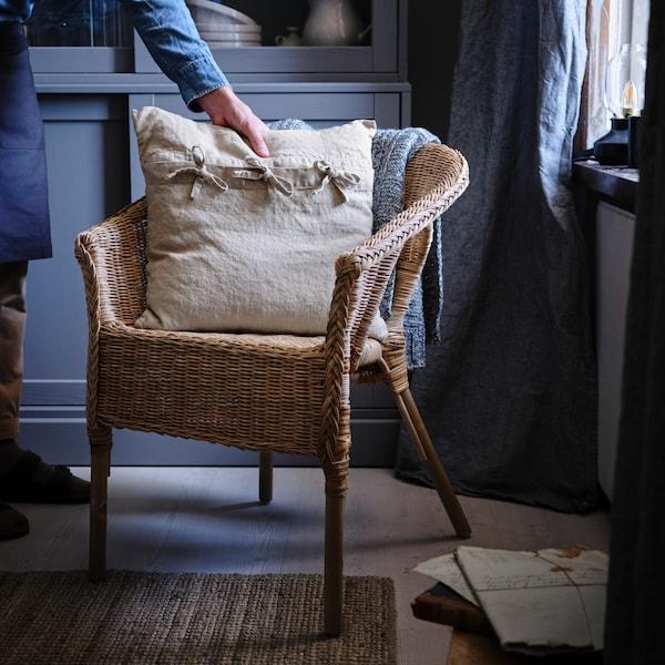 La main d'une personne arrangeant un coussin sur un fauteuil en rotin/bambou.