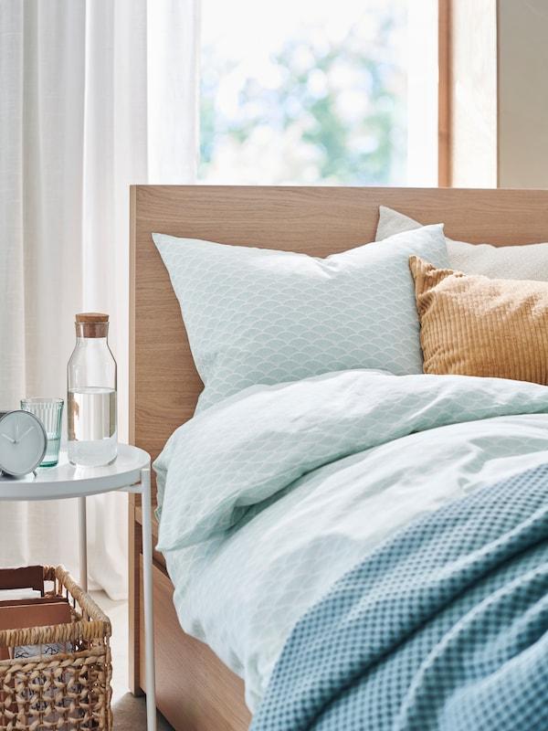 Eine Nahaufnahme von einem holzfarbenen Bett mit pastellblauer Bettwäsche, einer blauen Tagesdecke und einem weissen, runden Nachttisch daneben.
