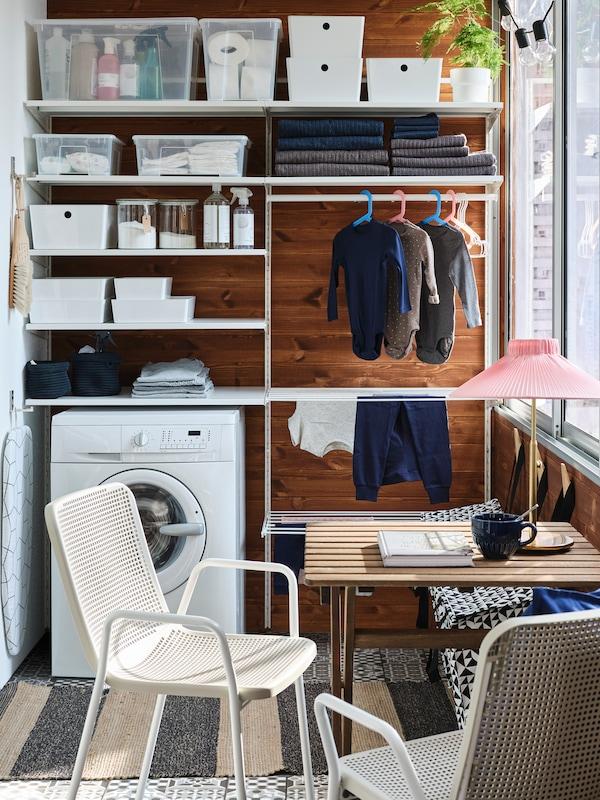 En balkong som nyttjas som tvässtuga, där ena väggen är fullmatad med förvaring och framför det står två vita stolar och ett träbord, på golvet ligger en randig matta.