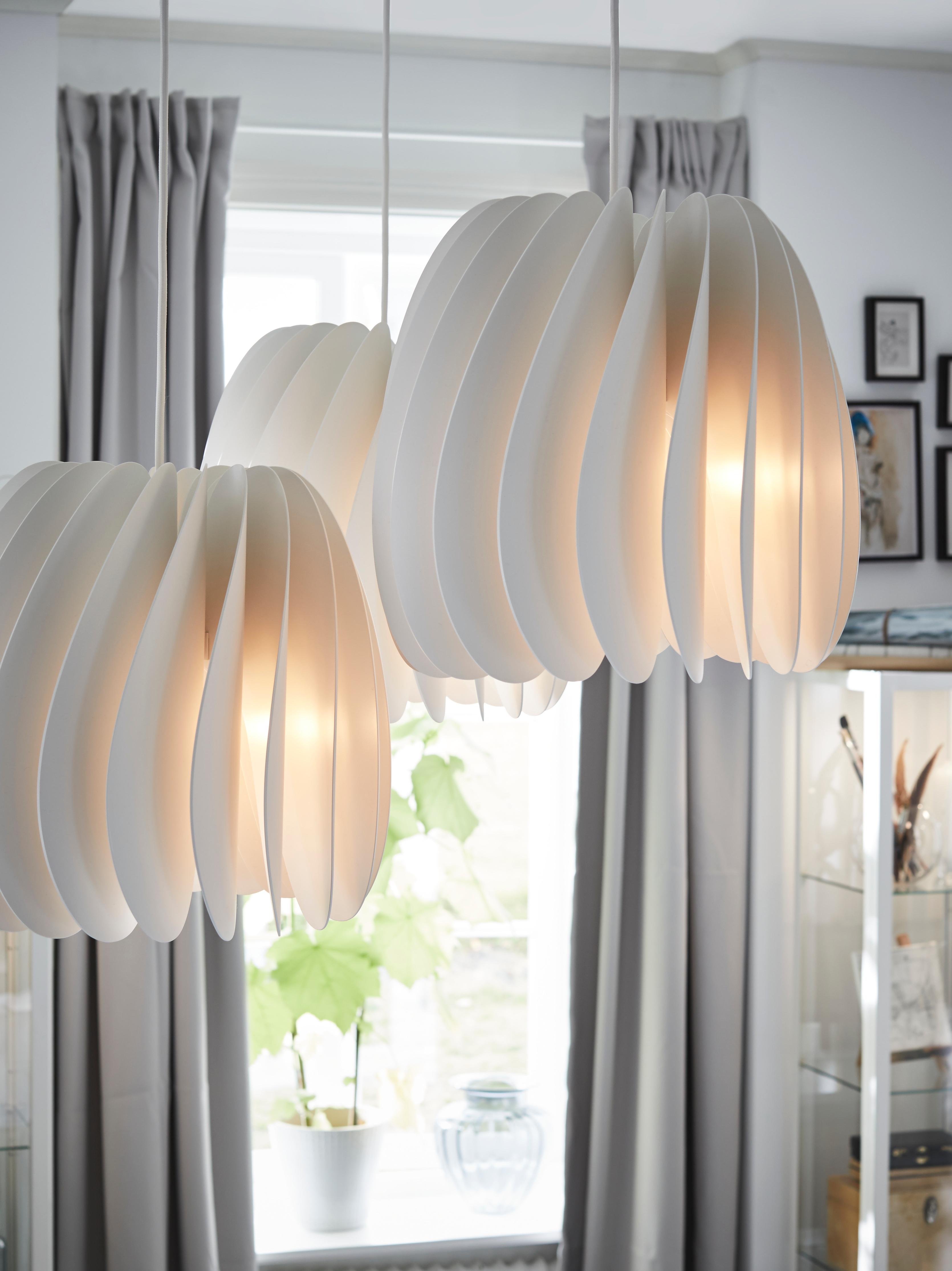 Trois suspensions lumineuses en plastique blanc SKYMNINGEN en forme de turbine sont montées dans une salle à manger.