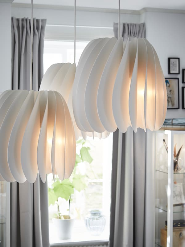 IKEA SKYMNINGEN white pendant lamps emitting soft light from a white slatted lampshade.
