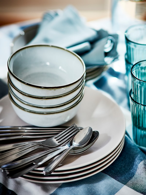 Some grey GLADELIG bowls stacked on top of grey plates with cutlery standing on a table next to some blue glasses.