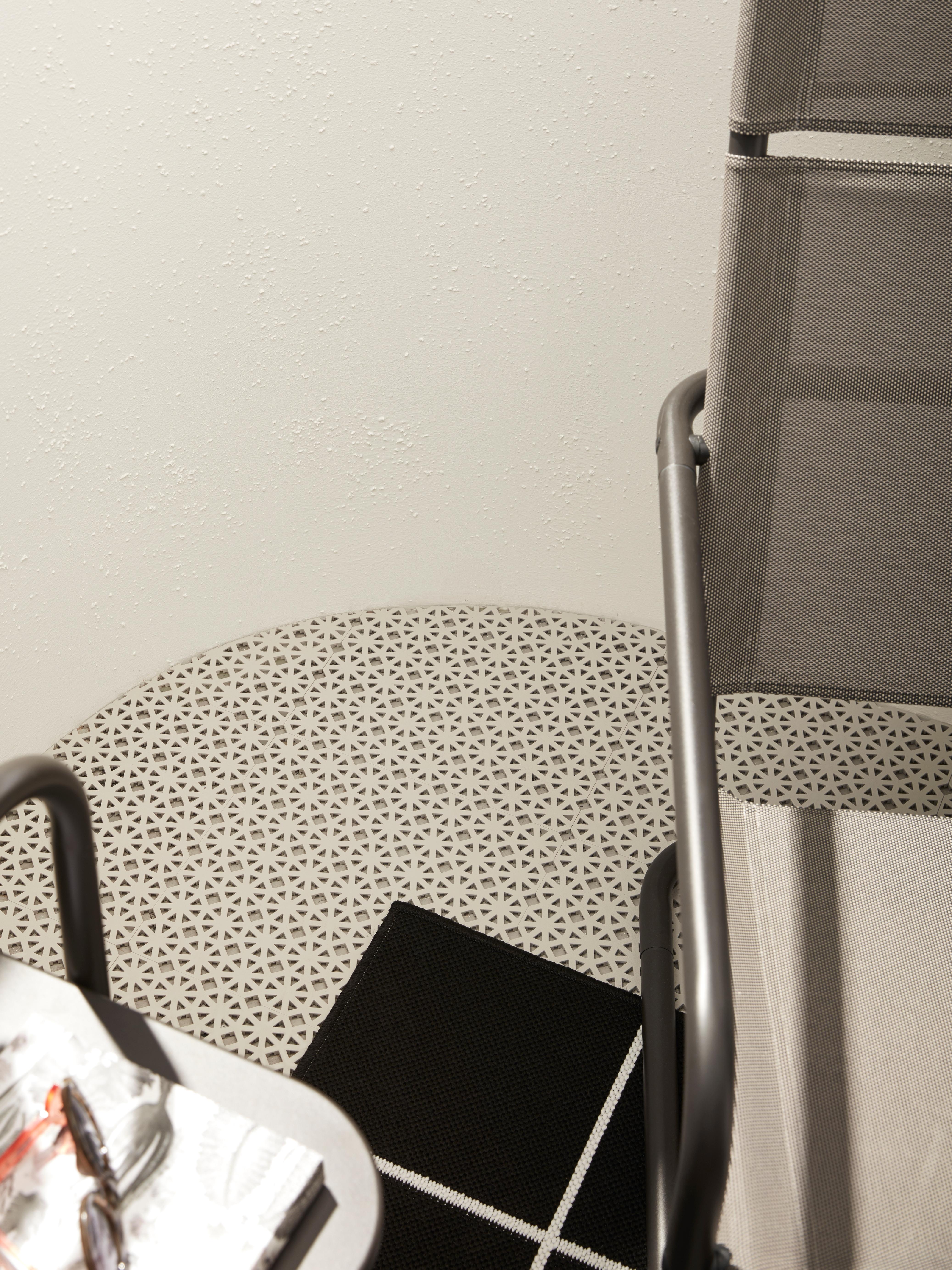 Svetlosiva ALTAPPEN podna obloga prati zaobljeni ugao balkona i nalazi se ispod fotelje, stočića i tepiha.