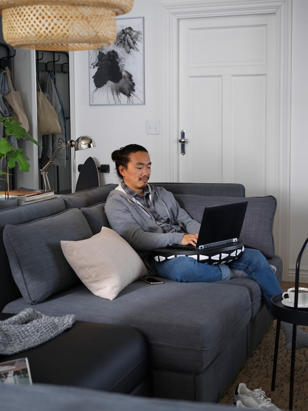 A man sits on a modular, dark grey/black VALLENTUNA sofa and types on a computer using a BYLLAN laptop support.