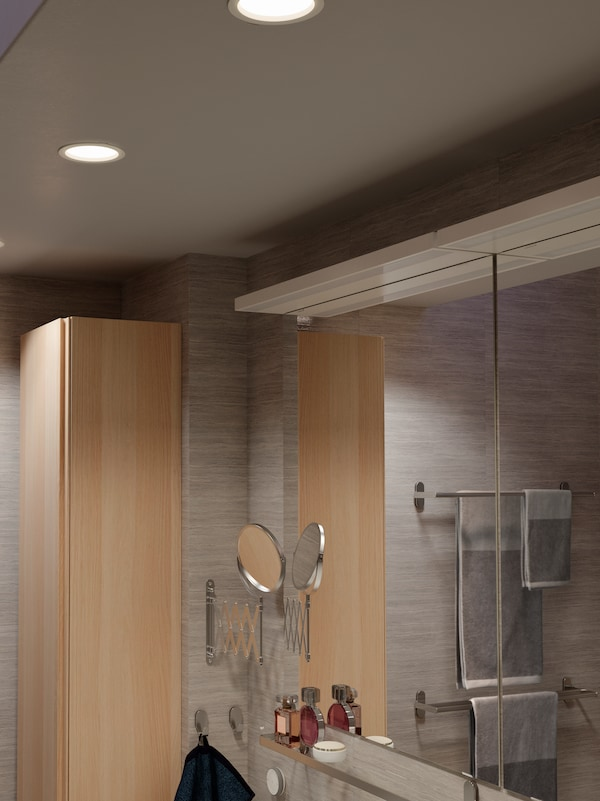 Bathroom ceiling with three LED recessed spotlights that are dimmable, a TRÅDFRI remote is mounted on the wall below.