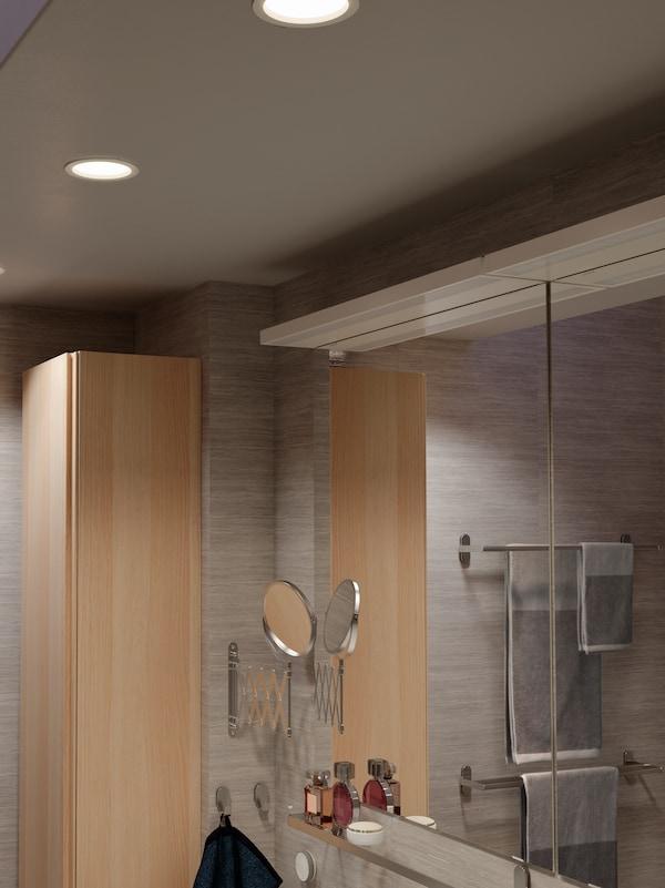 سقف حمام مع ثلاثة أضواء LED موجّهة غائرة قابلة للتخفيف، مع جهاز تحكم عن بعد TRÅDFRI مثبّت على الحائط بالأسفل.