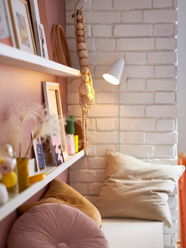 Deux rangées de cimaises MOSSLANDA blanches, des photos encadrées, des accessoires, une applique et un banc blanc avec des coussins.