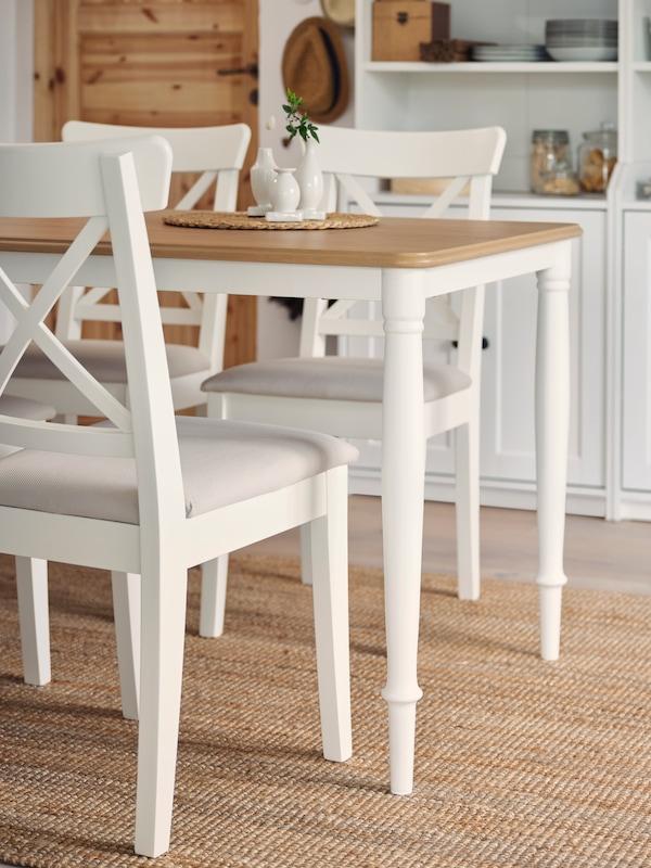 Trije beli stoli ter miza v beli barvi in barvi hrasta s cevastimi nogami na preprogi iz jute. V ozadju sta dve visoki beli omari.