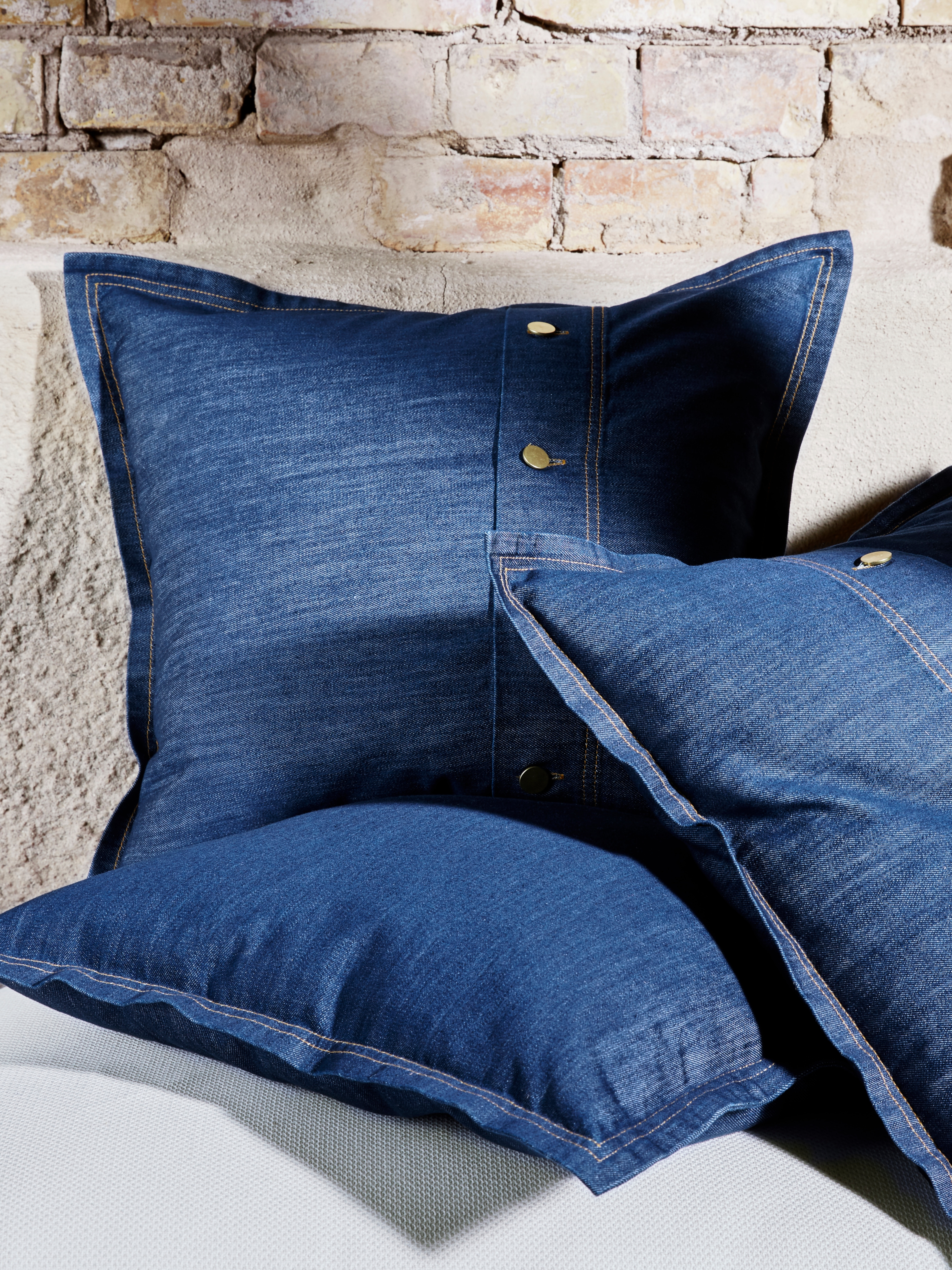 Three SISSIL cushion covers, with dyed blue denim and jean-inspired golden buttons and stitching details.