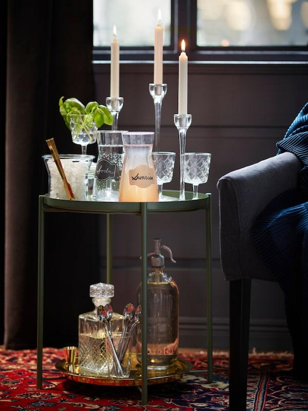 Gladom grönt sidobord används som drinkbord där is karaffer och glas samsas.