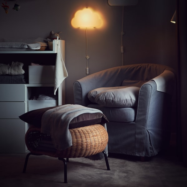 A cushion on a rattan GAMLEHULT footstool with storage in front of an armchair in a room lit by a night wall lamp.