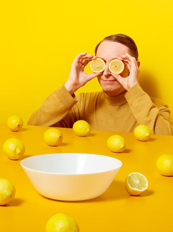 Egy sárga ruhát viselő férfi citromkarikákat tart a szeme előtt egy sárga asztal mellett, amin egész citromok vannak szanaszét, valamint egy fehér tál.