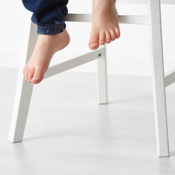 Close-up van de voeten van een kind op de voetsteun van een INGOLF kinderstoel.