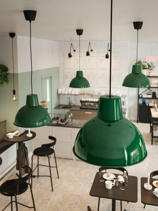 Lampade a sospensione verde scuro appese al soffitto di un bar con pareti verdi e bianche, tavoli e sedie antracite e un bancone.