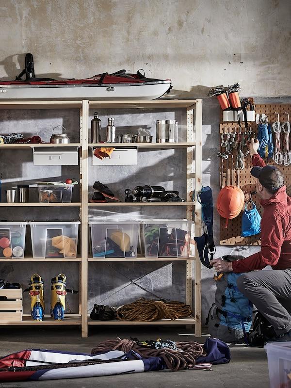 Muž si bere z police vedle policového dílu IVAR potřebné nářadí. Na polici jsou krabice SAMLA s  nástroji a dalšími předměty.