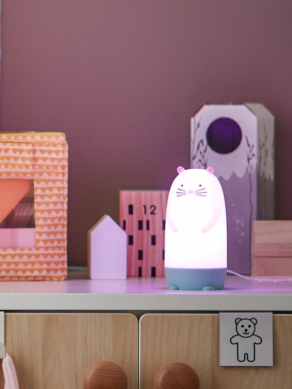 Kabinet pada dinding berwarna ungu dengan mainan kanak-kanak di atasnya di samping lampu malam dalam bentuk watak yang comel.