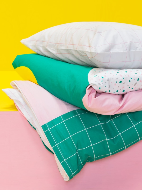 A pillow lies on top of a folded duvet. They are inside a MÖJLIGHET pillowcase and quilt cover with a graphical pattern.