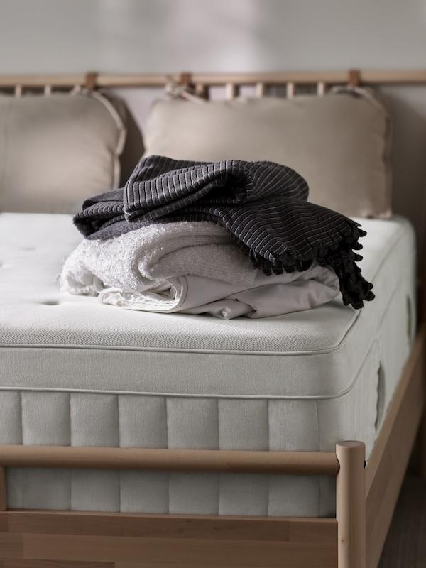 Närbild på HESSTUN madrass i BJÖRKSNÄS sängstomme, utan lakan på men med en vikt hög av plädarna EVALI, i vitt, och TJÄRBLOMSTER i mörkt grå liggandes på.