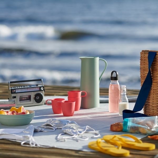 A picnic at the seaside, with colourful reusable plastic mugs and dinnerware.