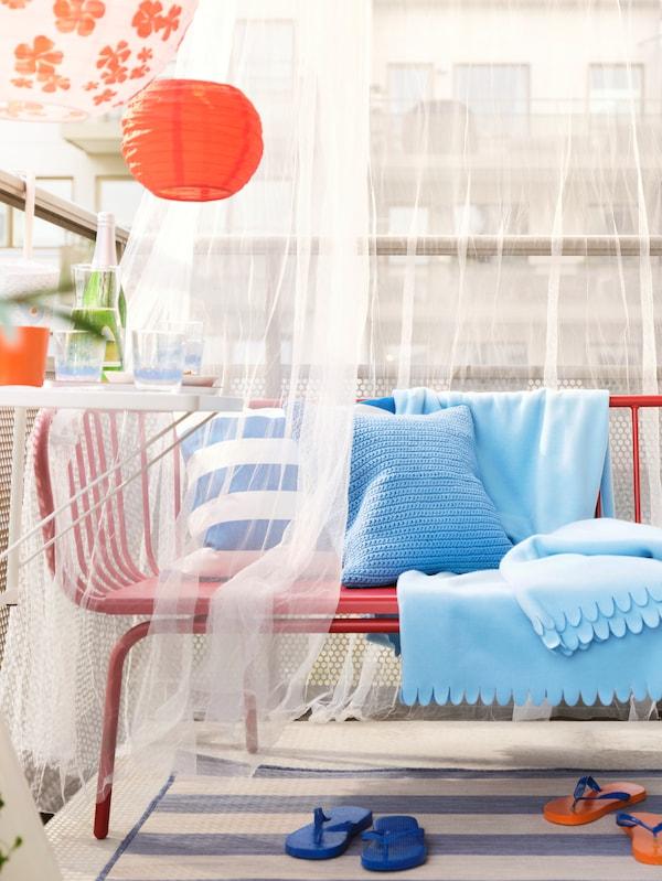 Rode Brusen bank met verschillende blauwe getinte kussens en plaids ingelegd met daarrond witte doorschijnende gordijnen