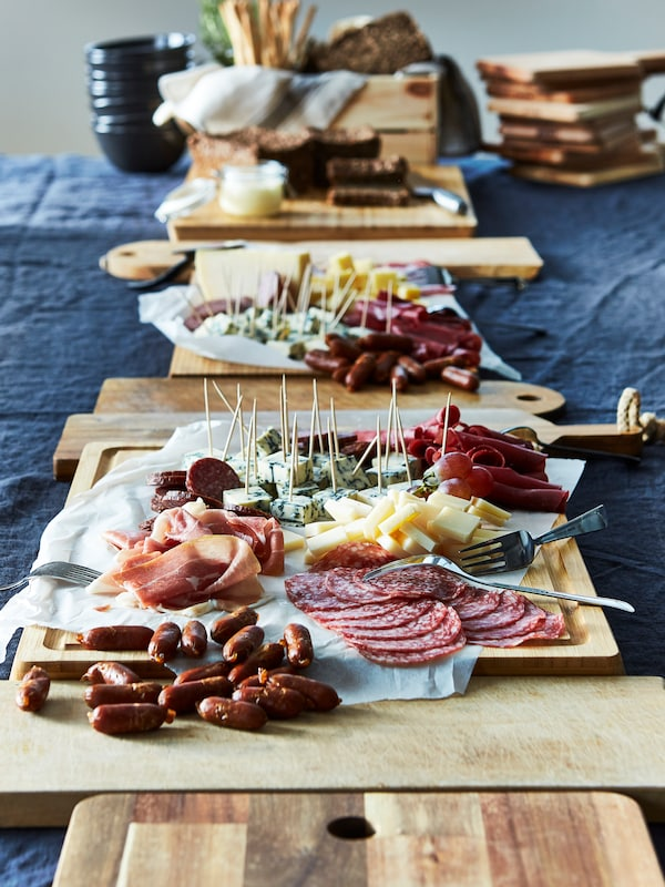 Chopping boards in a line with meat and cheese on sticks including OST PRÄST and OST BLÅMÖGEL, on a table with a blue cloth.