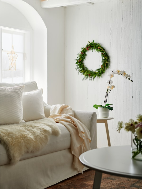 A living room in white and beige, with accents of greenery.