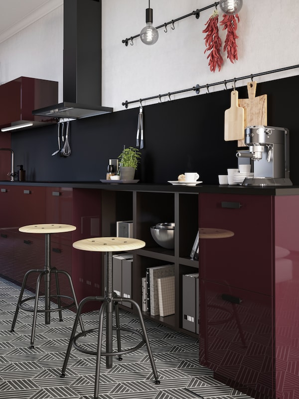 Two stools in pine/black stand by a kitchen countertop in a burgundy kitchen. A coffee machine and some mugs are on top.