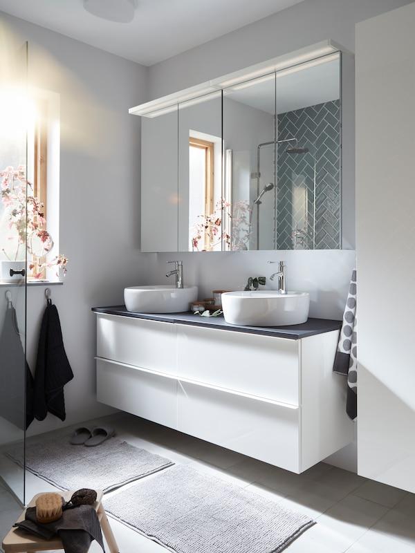 Шафа під раковину з темно-сірою стільницею та двома білими раковинами, дві дзеркальні шафи з подвійними дверцятами та два килимки.