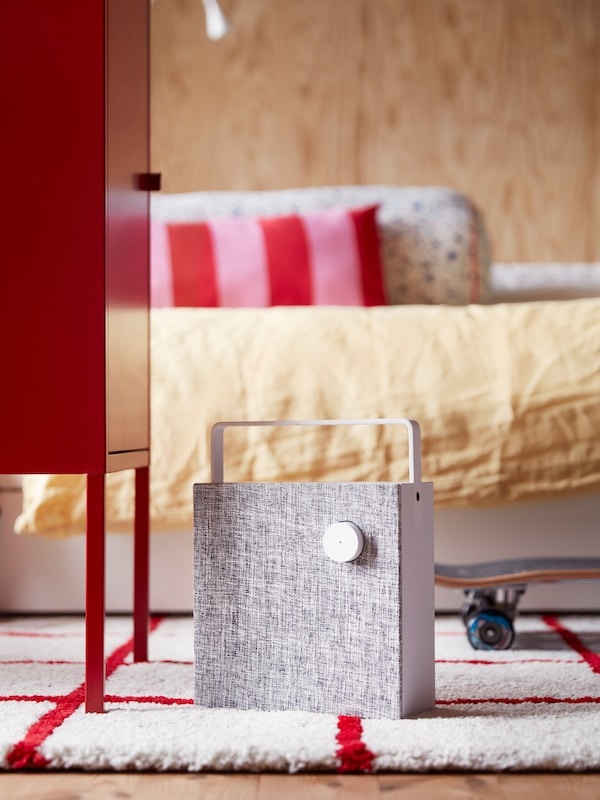 A white, portable ENEBY bluetooth speaker standing on a white-red rug in front of a bed with cushions in a teen's room.