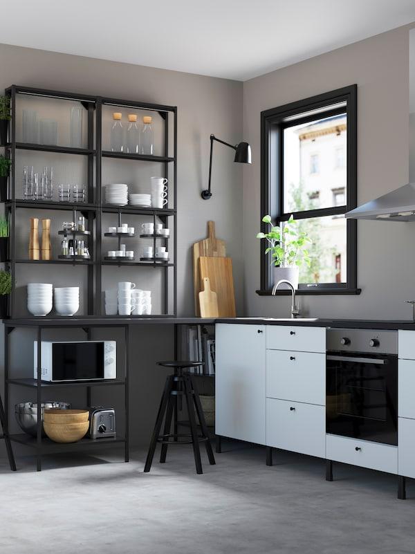 Otmena crna i bela ENHET kuhinja s posuđem, čašama i uređajima, na otvorenim policama.