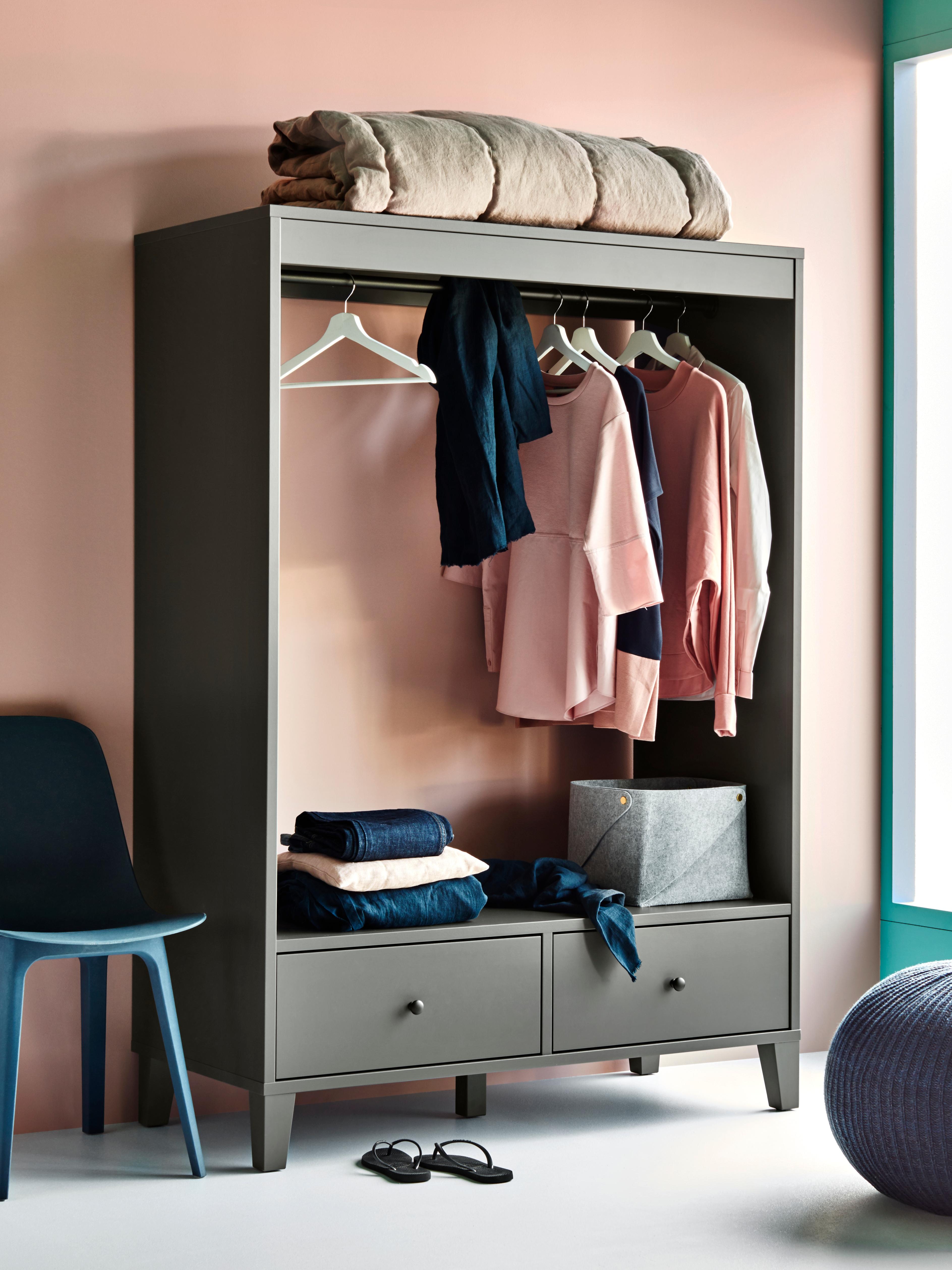 Une armoire ouverte BRYGGJA grise à côté d'une chaise bleue, contenant des vêtements roses et bleus et une boîte PUDDA en feutre gris.