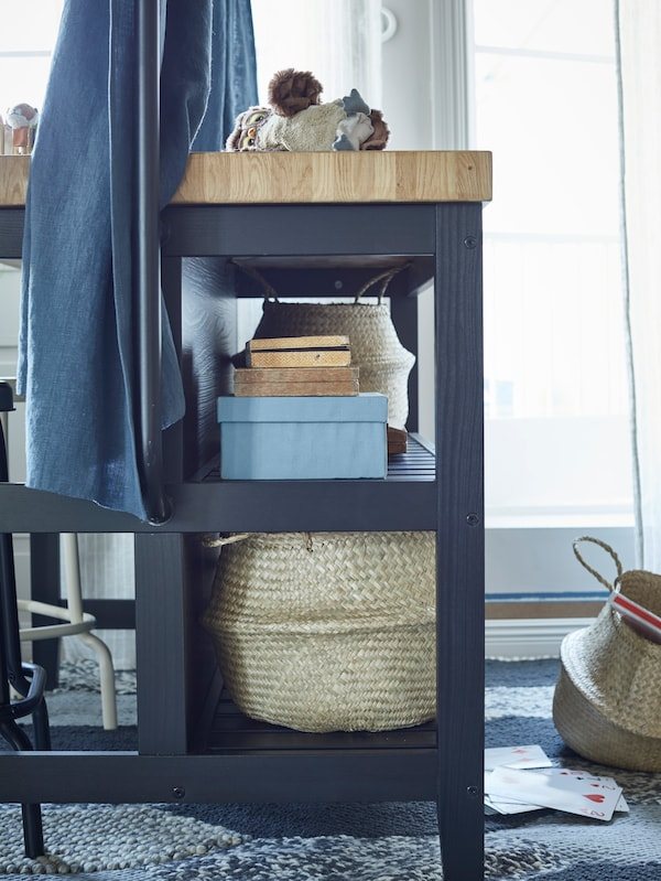 Three seagrass baskets and books on the lower shelves of a kitchen island in blue/oak that is being used as a desk.