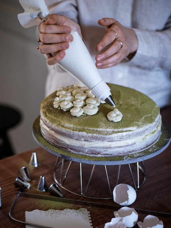 A person squeezes out whirls of icing onto a cake, using piping tubes from the SMAKSAM cake decoration set.