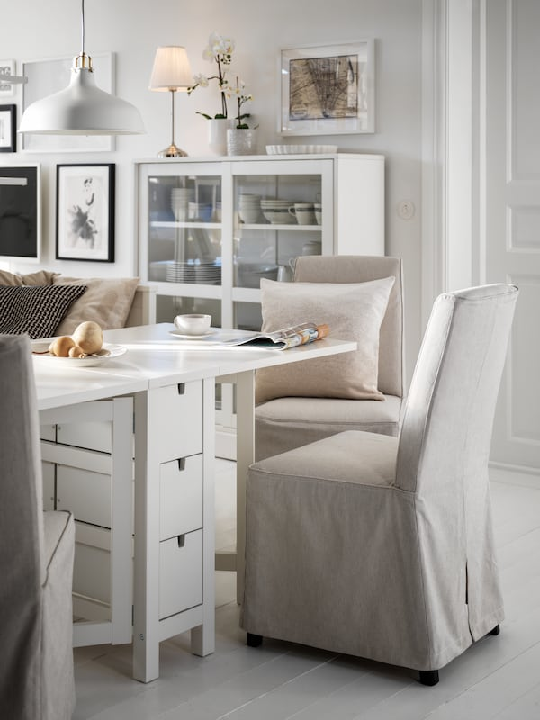 A white NORDEN gateleg table surrounded by beige BERGMUND chairs. A white HAVSTA glass-door cabinet stands by a nearby wall.