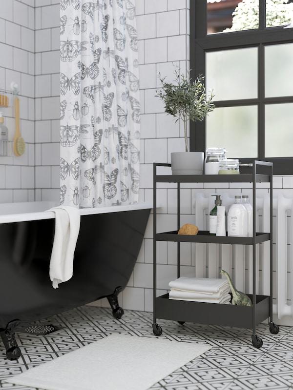 En svart rullvagn med handdukar och duschprodukter, ett svart badkar, en vit badrumsmatta och ett duschdraperi med fjärilsmönster.