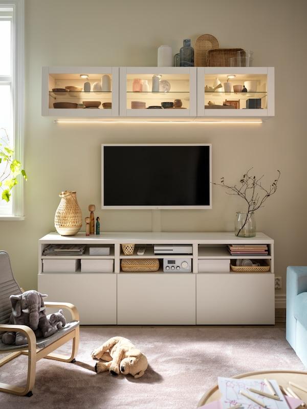 ทีวีติดผนังที่มีตู้ BESTÅ/เบสตัว สีขาวอยู่ด้านล่าง และมีตู้ BESTÅ/เบสตัว สีขาวพร้อมบานกระจกอยู่ด้านบนตั้งโชว์ชามและแจกัน