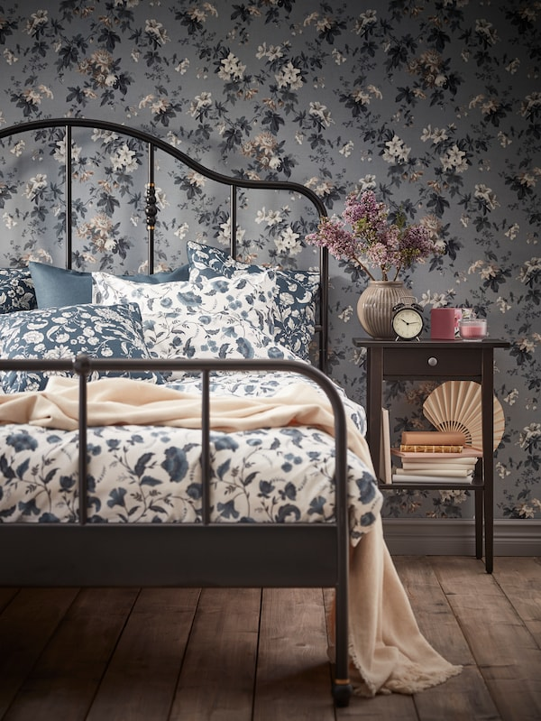 A SAGSTUA bed with KÄLLFRÄNE bed linen stands next to a HEMNES bedside table against a wall with floral wallpaper.