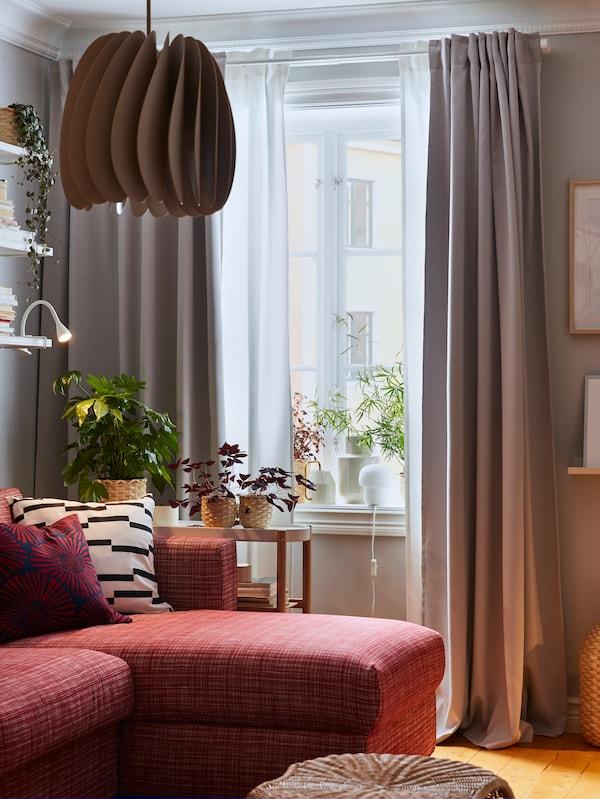 Eine beigefarbene Hängeleuchte, ein rotes Sofa, Hocker aus Rattan, weisse und graue Gardinen und Pflanzen auf der Fensterbank.