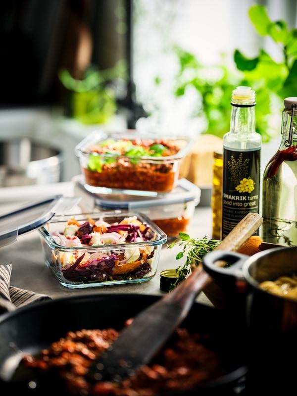 Eine Flasche SMAKRIK Rapsöl auf einer sonnigen Arbeitsplatte umgeben von gegarten Speisen. Einige davon sind in IKEA 365+ Behältern verpackt.