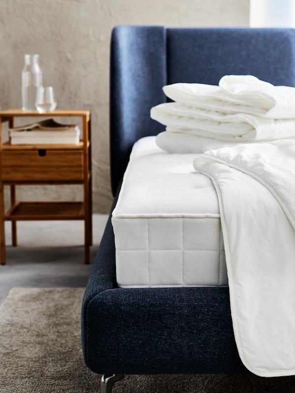 غرفة نوم بها هيكل سرير أزرق منجد TUFJORD ومرتبة بيضاء بدون غطاء وألحفبيضاء مطوية في الأعلى.
