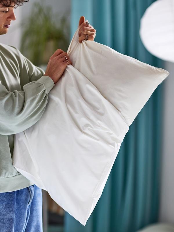 Un hombre poniendo a una almohada el protector LUDDROS; al fondo hay una planta, unas cortinas y una lámpara de techo.