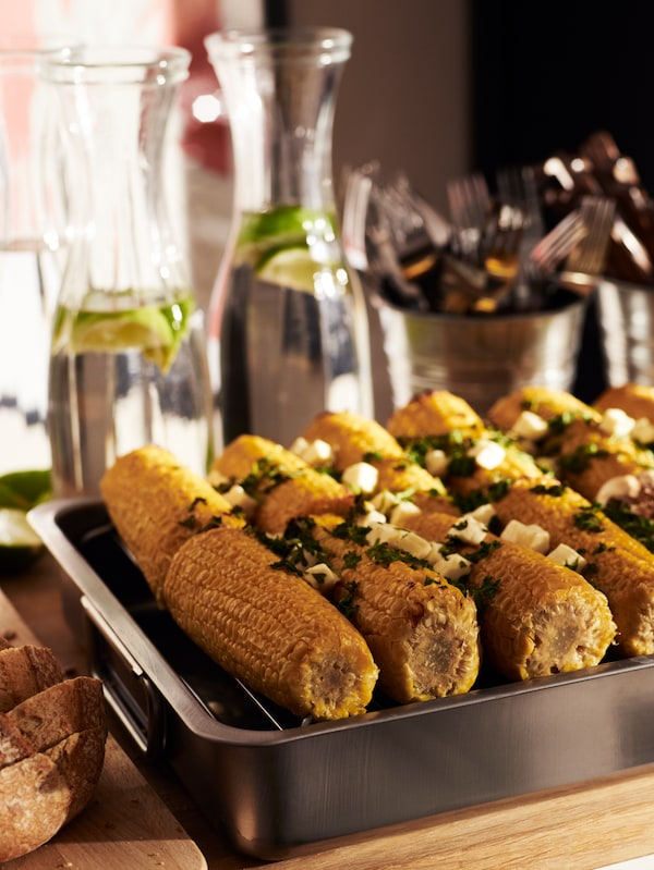 Grilled corn on the cob in a stainless-steel roasting tin with grill rack. Cutlery and glass carafes are in the background.