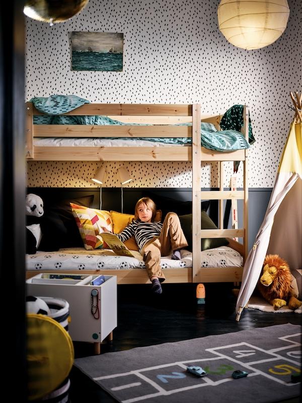 Ein schwarz-weiß gestaltetes Zimmer, in dem ein Kind sich in die untere Etage eines MYDAL Etagenbettes lehnt. Es ist umgeben von verschiedenen Spielzeugen.