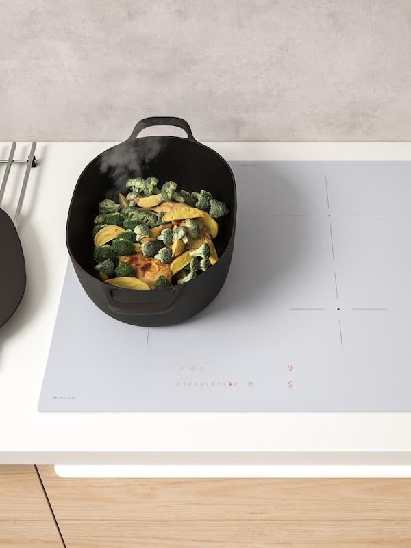 Casseruola fumante in ghisa contenente pollo, broccoli e patate su un piano cottura a induzione bianco BEJUBLAD.
