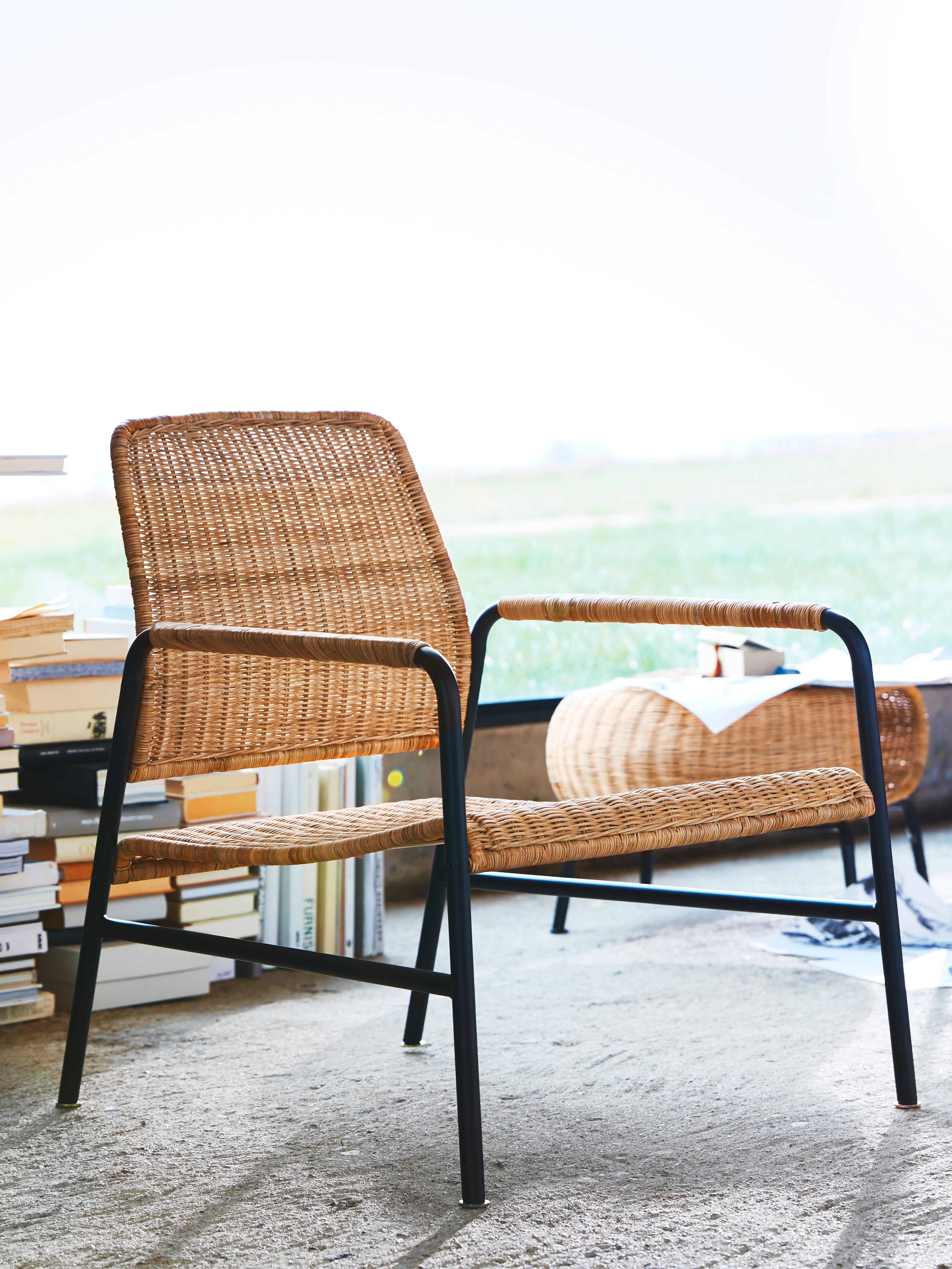 Ratanezko eta antrazita koloreko ULRIKSBERG besaulkia ratanezko eserleku zabal eta baxu batekin eta marko beltz batekin, liburu pila baten eta leiho baten aurrean nabarmenduta.