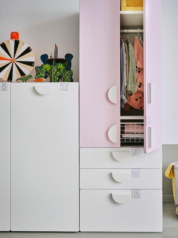 Un dulap SMÅSTAD cu unitate glisantă și unul din sertare stau unul lângă celălalt. Unele jucării stau deasupra unui dulap.