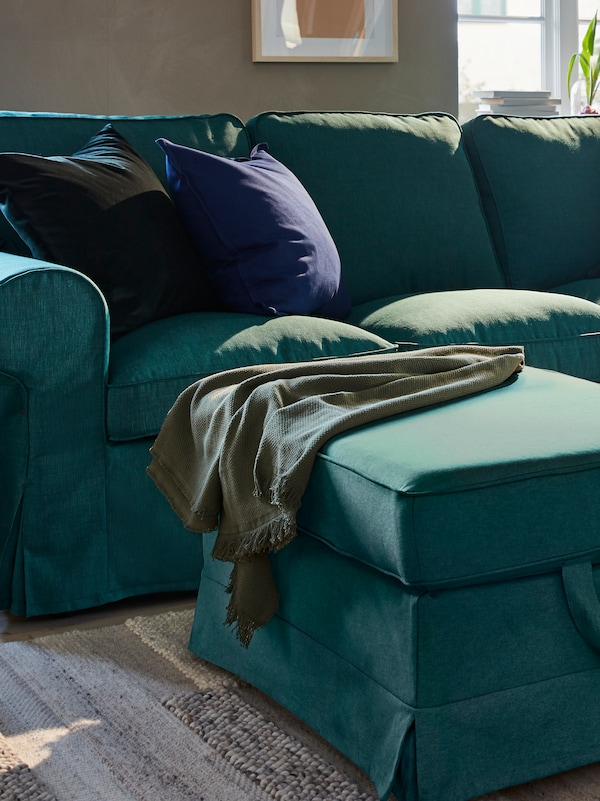 A living room with a dark turquoise sofa and foot stool with cushions and a blanket, on a handwoven off-white rug.