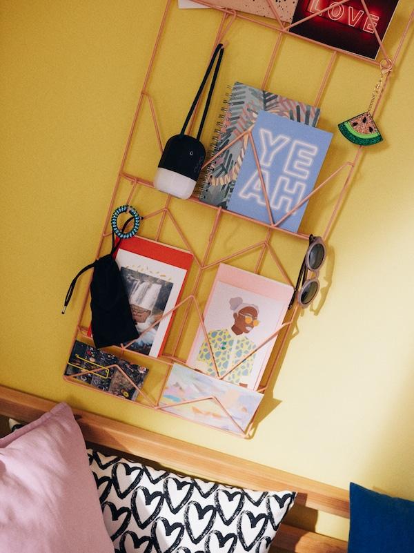Un panou de afișaj KVICKSUND pe un perete de culoare galbenă, pe care se află ilustrate, ochelari de soare, caiete, fotografii și brelocuri, deasupra unor perne decorative colorate.